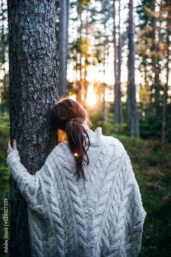 Woman leaning against a tree during sunset in autumn - 328027339