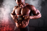 Bodybuilder male African uses electronic belt muscle stimulator trainer abdominal muscles on a black background with smoke