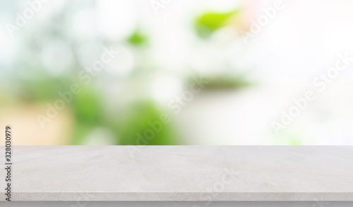 abstract blurred garden view form living room window with concrete table counter background for show , promote ,design banner ads on display concept