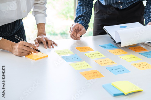 Two creative business people meeting and planning use post it notes sticky note on desk to share idea, Analysis data chart and graph with teamwork strategy brainstorming in office