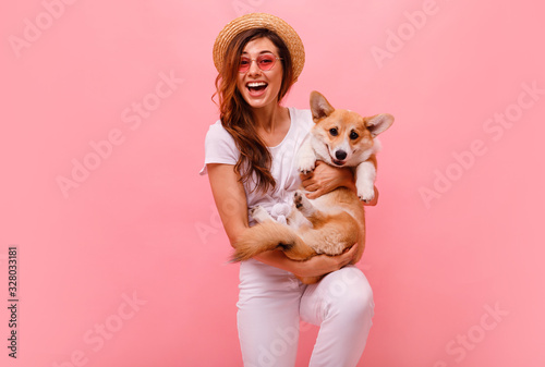 Photo Cute brunette woman in white t shirt and jeans holding and embracing corgi puppy dog on plane pink background