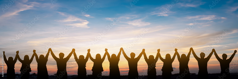 Fototapeta Silhouette of group happy business team making high hands over head in beautiful sunset sky evening time for business success and teamwork concept in company