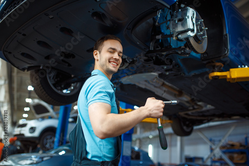mata magnetyczna Repairman repairing vehicle on lift, car service