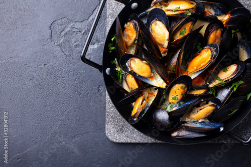 Fotografiet Mussels with herbs and sauce in black pan. Copy space. Top view.