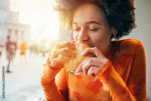 Leinwand Poster Young beautiful multiethnic woman eating hamburger