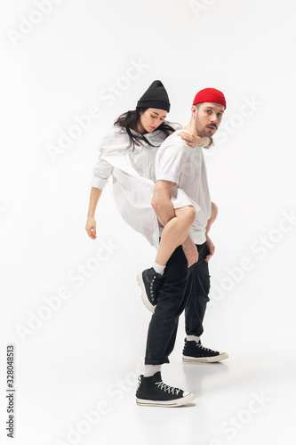 Youth. Trendy fashionable couple isolated on white studio background. Caucasian woman and man posing in basic minimal stylish clothes. Concept of relations, fashion, beauty, love. Copyspace. Wall mural