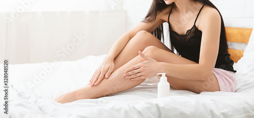 Fototapeta Young woman pampering her legs with moisturizing cream
