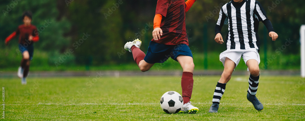Fototapeta Young Athletes Kicking Soccer Ball on Wet Grass Field. Youth Football Players In Run Duel