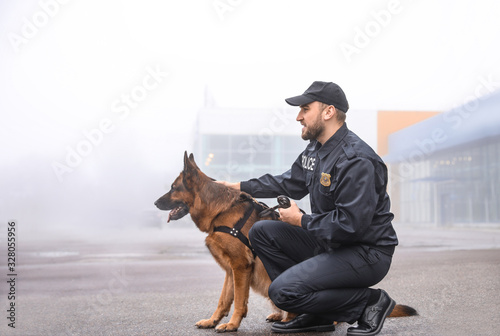 Foto Male police officer with dog patrolling city street