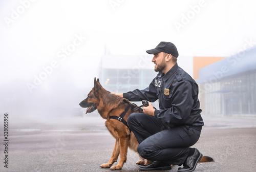 Obraz Male police officer with dog patrolling city street - fototapety do salonu