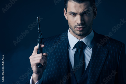 Photographie Front view of gangster holding gun and looking at camera on dark blue background