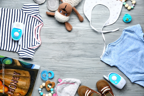 Frame made of baby clothes and accessories on wooden background