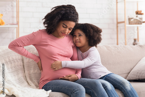 Fotografía Caring little daughter comforting pregnant mom that suffering from prenatal cont