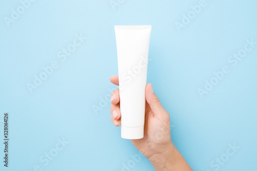 Leinwand Poster Young woman hand holding and showing white tube on light blue background