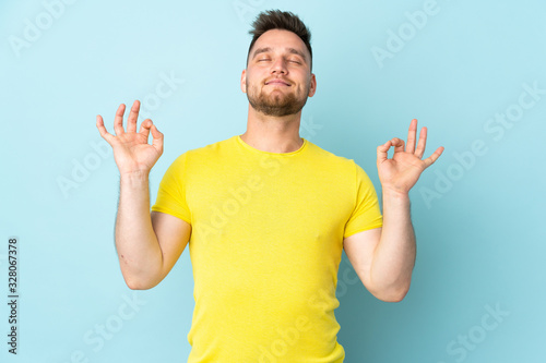 Russian handsome man isolated on blue background in zen pose