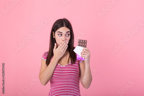 Portrait of a happy young woman with chocolate bar isolated over pink background covenring her mouth Wallpaper Mural