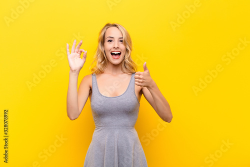 young blonde woman feeling happy, amazed, satisfied and surprised, showing okay Wallpaper Mural