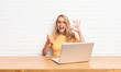 canvas print picture - young blonde woman feeling happy, amazed, satisfied and surprised, showing okay and thumbs up gestures, smiling using a laptop