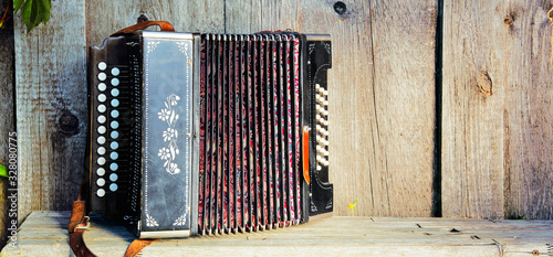 Photo Old lonely accordion on the bench in summer sunny weather