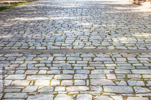 Stone paved footpath, cobblestone pathway background texture.