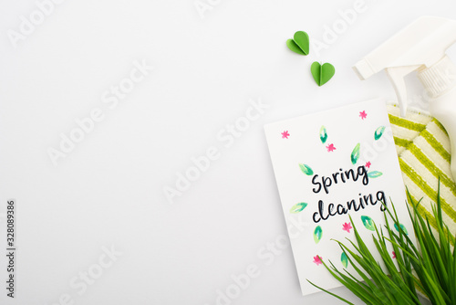 top view of green grass and cleaning supplies near spring cleaning card on white Fototapeta