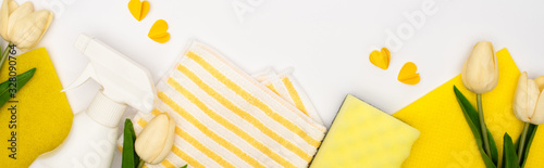 top view of spring tulips and yellow cleaning supplies with hearts on white background, panoramic shot