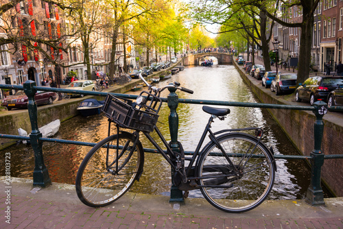 Amsterdam city in Netherlands with bycicles beside a canal Canvas Print