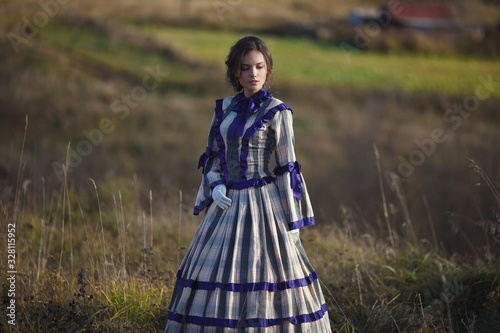 Photographie beautiful girl in a suit of the 19th century walks in the village