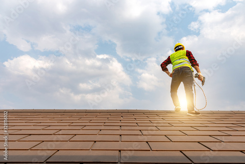 Fotografie, Obraz Construction workers lay a roof with a nail gun to develop a large commercial building