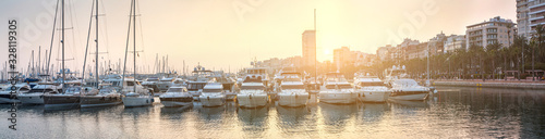 Obraz Breathtaking romantic summer panoramic view of boats and yachts in harbor in evening sunshine glow. Costa Blanca. Alicante, province of Valencia, Spain. - fototapety do salonu