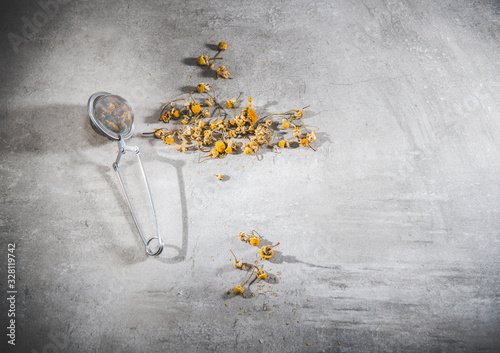 Dry chamomile tea petals - loose flowers in a infuser on gray table Fototapet