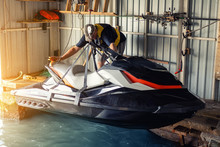 Senior Man Launching Or Lifting Modern Fast Jetski Hanged On Strpas With Wire Hoist Rail Crane For Dry Storage. Boat Garage Interior For Boats And Jet-ski Storage, Service And Maintenance