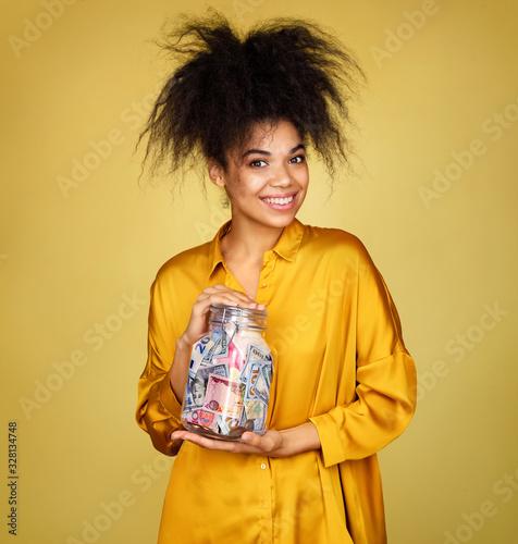 Smiling girl shows her saving money in glass jar Wallpaper Mural
