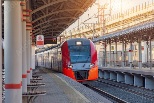 Fotografía Passenger electric subway train arrives at a platform with benches for people