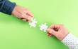 hands of two businessmen connecting matching jigsaw puzzle pieces against green background, business partnership and teamwork concept