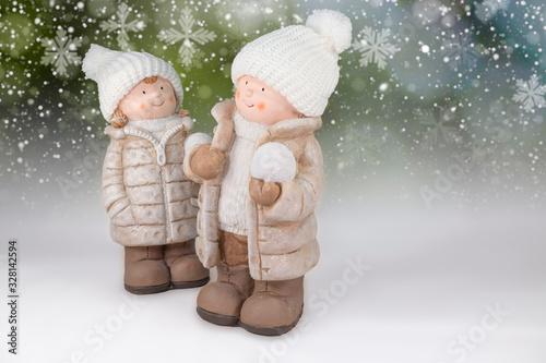 Fotografía Figuren eines Mädchen und Jungen mit weißer Wollmütze und Schneeball in der Hand