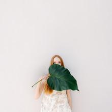 Minimalistic Portrait Of A Redhead Girl With Green Leaf