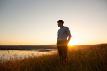 Man Standing And Enjoying The Beautiful Sunset Over A Wide River Valley. Young Man In  Blue Shirt And Black Pants Standing And Looking To River.