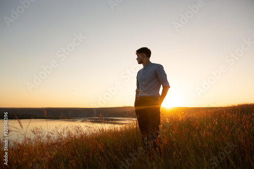 Obraz Man standing and enjoying the beautiful sunset over a wide river valley. Young man in  blue shirt and black pants standing and looking to river. - fototapety do salonu