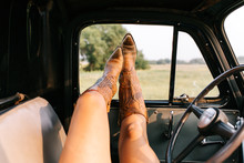 Girl With Cowboy Boots Hangs Legs Out Of Old Truck Window In Amarillo, TX