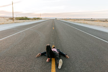 A Man Laying In The Middle Of The Road