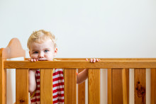 Portrait Of Baby Boy Leaning On Crib At Home