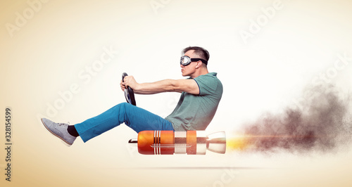Obraz na plátně Cool man in casual clothes with goggles holds a steering wheel in his hands while driving an alternative vehicle, on yellow background