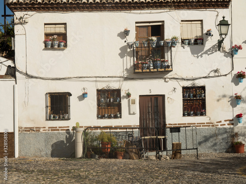 white facade of typical Andalusian house with bars and flower pots Wallpaper Mural