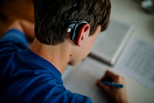 15 Yr Old Boy With Cochlear Implant Studying And Taking Notes
