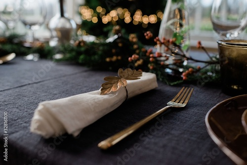 gold napkin holder on a decorated dinner table with candles - 328161100