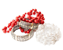 Female Bijouterie On A White Background: Red And Pearl Beads, Golden Bracelets