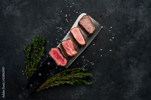 Four steaks on knife on a stone background. Four types of meat frying Rare, Medium, Medium Good, Well done