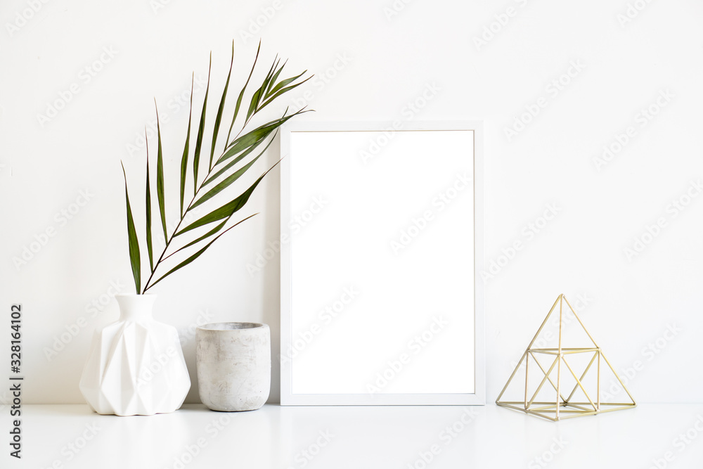 Fototapeta White frame and home decoration details on tabletop with wall, artwork poster mock-up