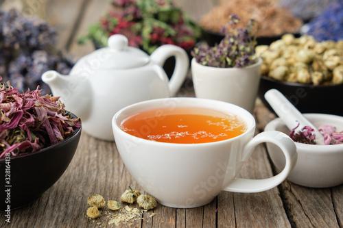 Fototapeta Healthy herbal tea cup. Teapot and  medicinal herbs on table. Herbal medicine. obraz